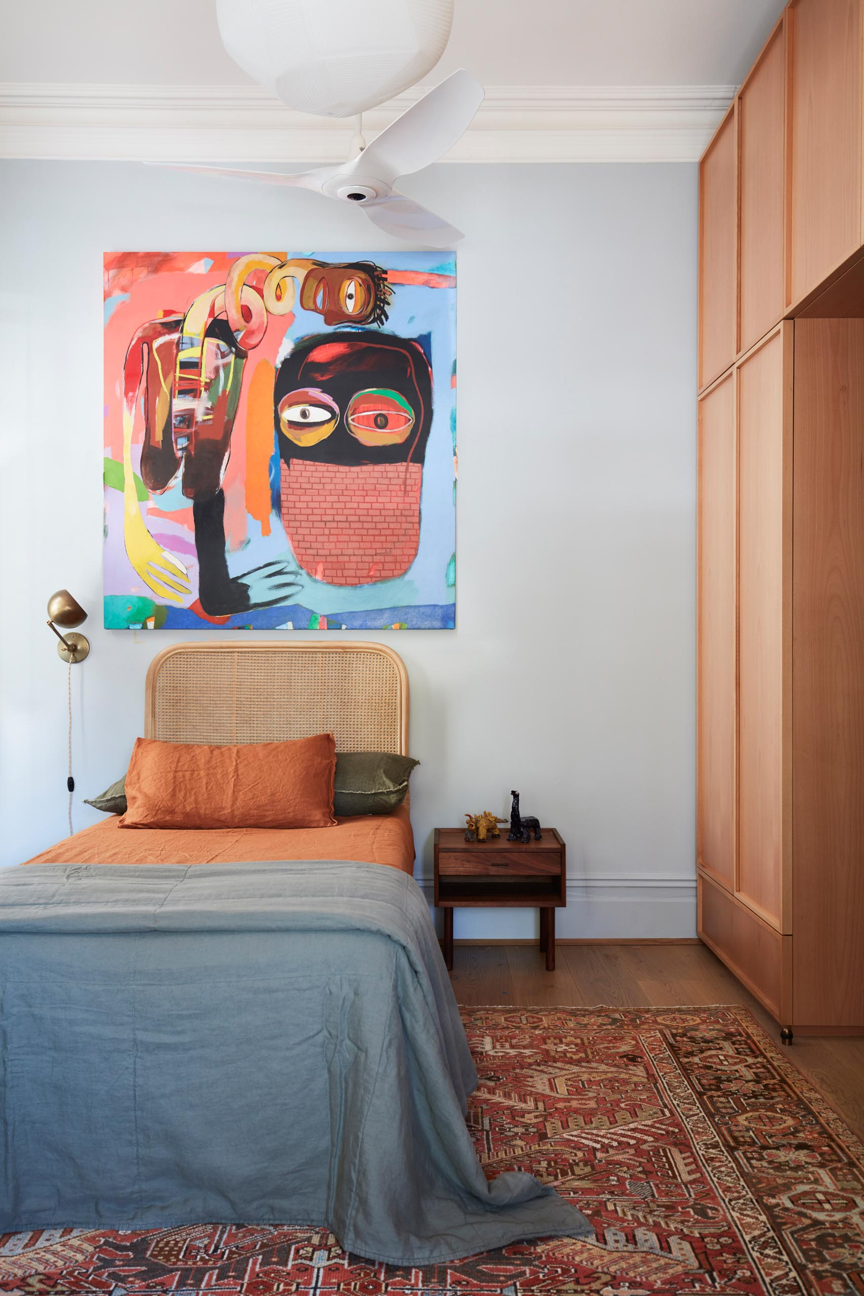 A bedroom with a bold and colorful art piece above the bed.