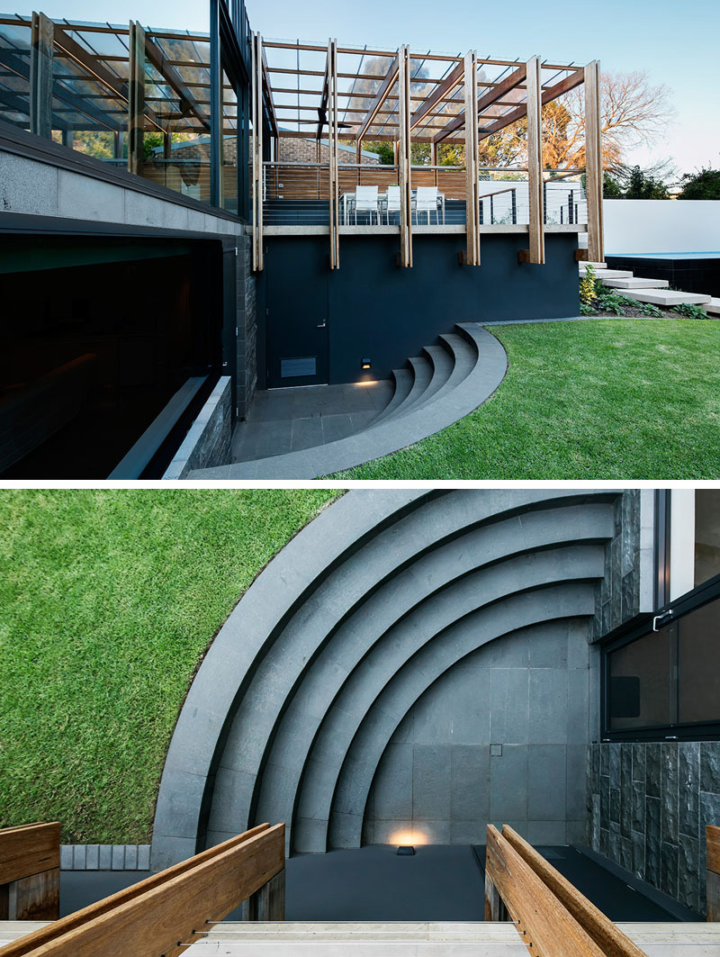 Curved stone steps lead from the lower level of this modern house extension to the backyard. The location of the steps prevents them from being a hazard when the kids are playing and the way they curve into the side of the home makes them a unique design detail.
