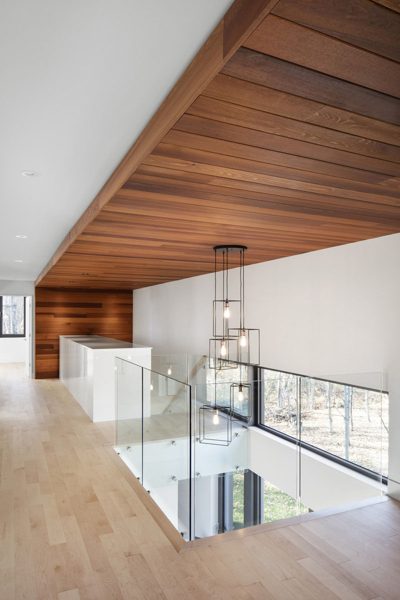 As you head upstairs in this home, you're greeted by large cedar wood slats that wrap from the floor to the ceiling, and back down to the floor.