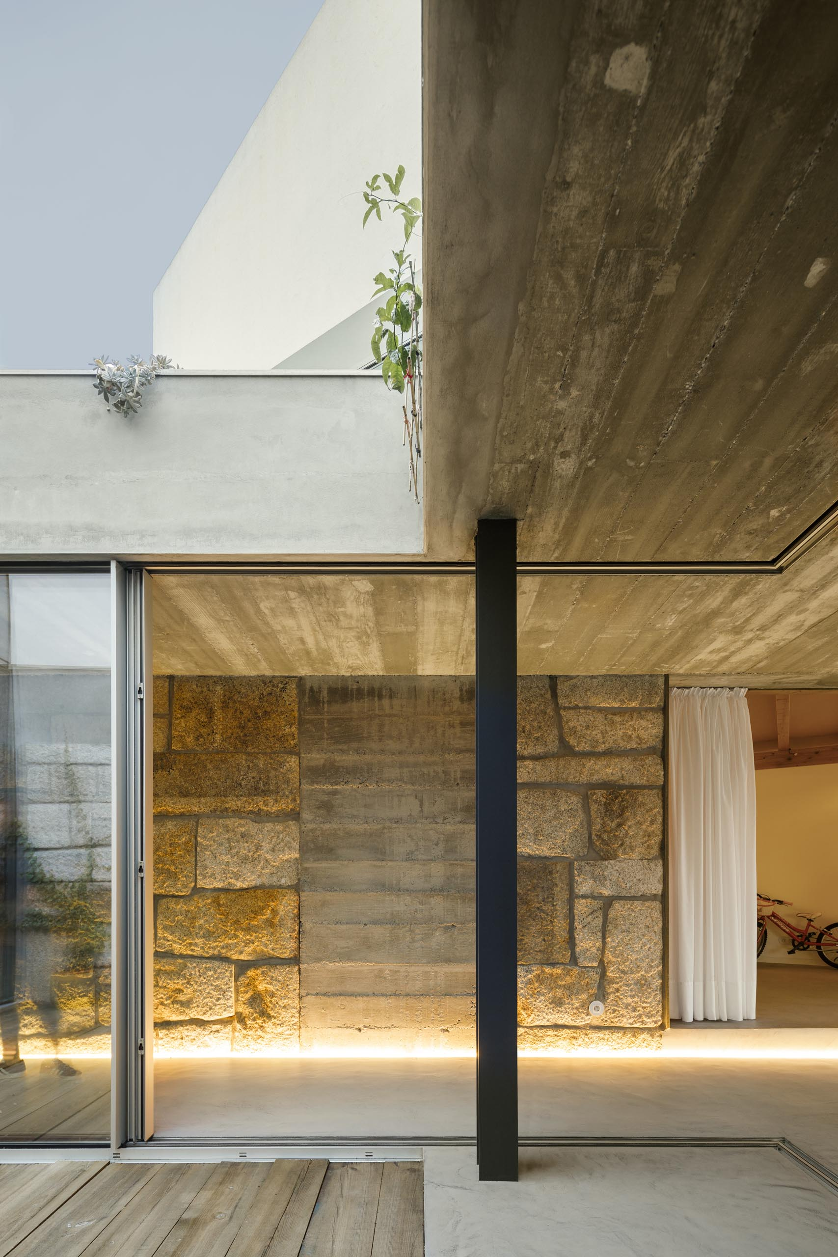 By using illuminated LED strips, the stone, concrete, and wood walls throughout this modern home are able to be showcased in a subtle way.