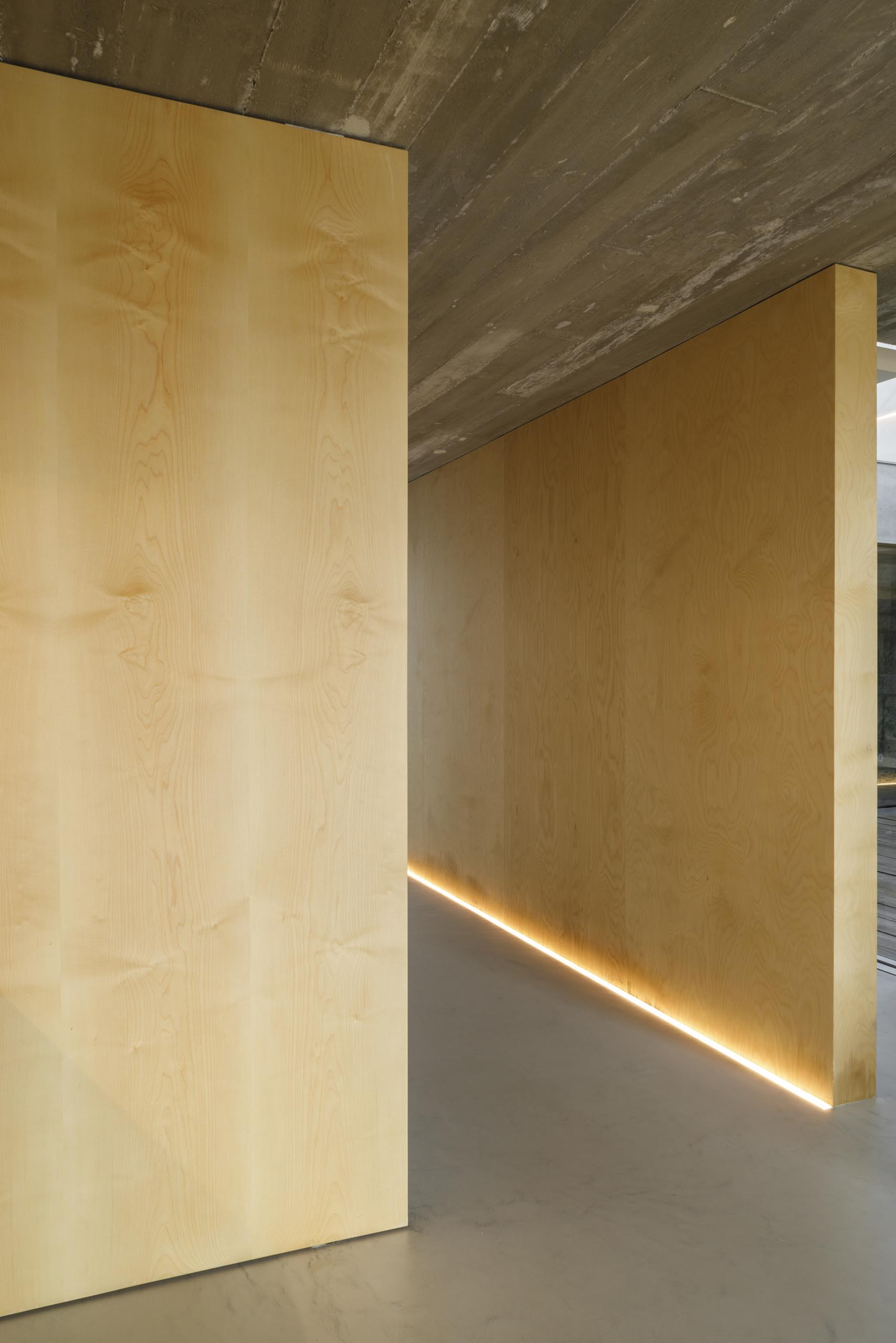 A hallway with wood walls is illuminated by LED lighting on the floor.