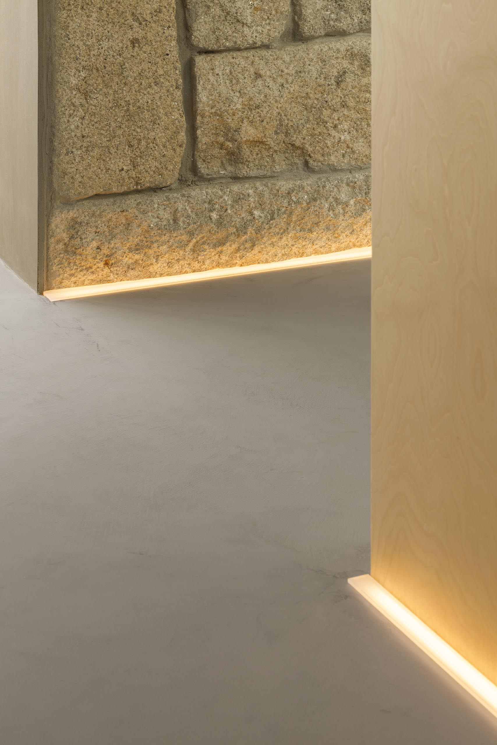 A hallway with stone and wood walls is illuminated by LED lighting on the floor.