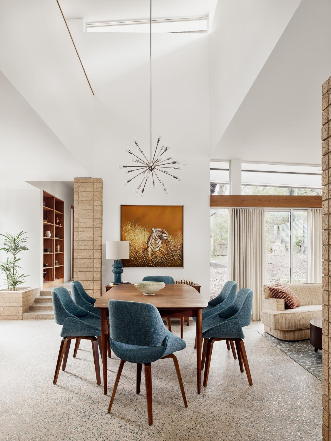 In this mid-century modern inspired dining room, there's a dark wood table with matching chairs that add a pop of color to the open plan interior. A Sputnik inspired pendant light draws the eye upwards to the high ceiling.