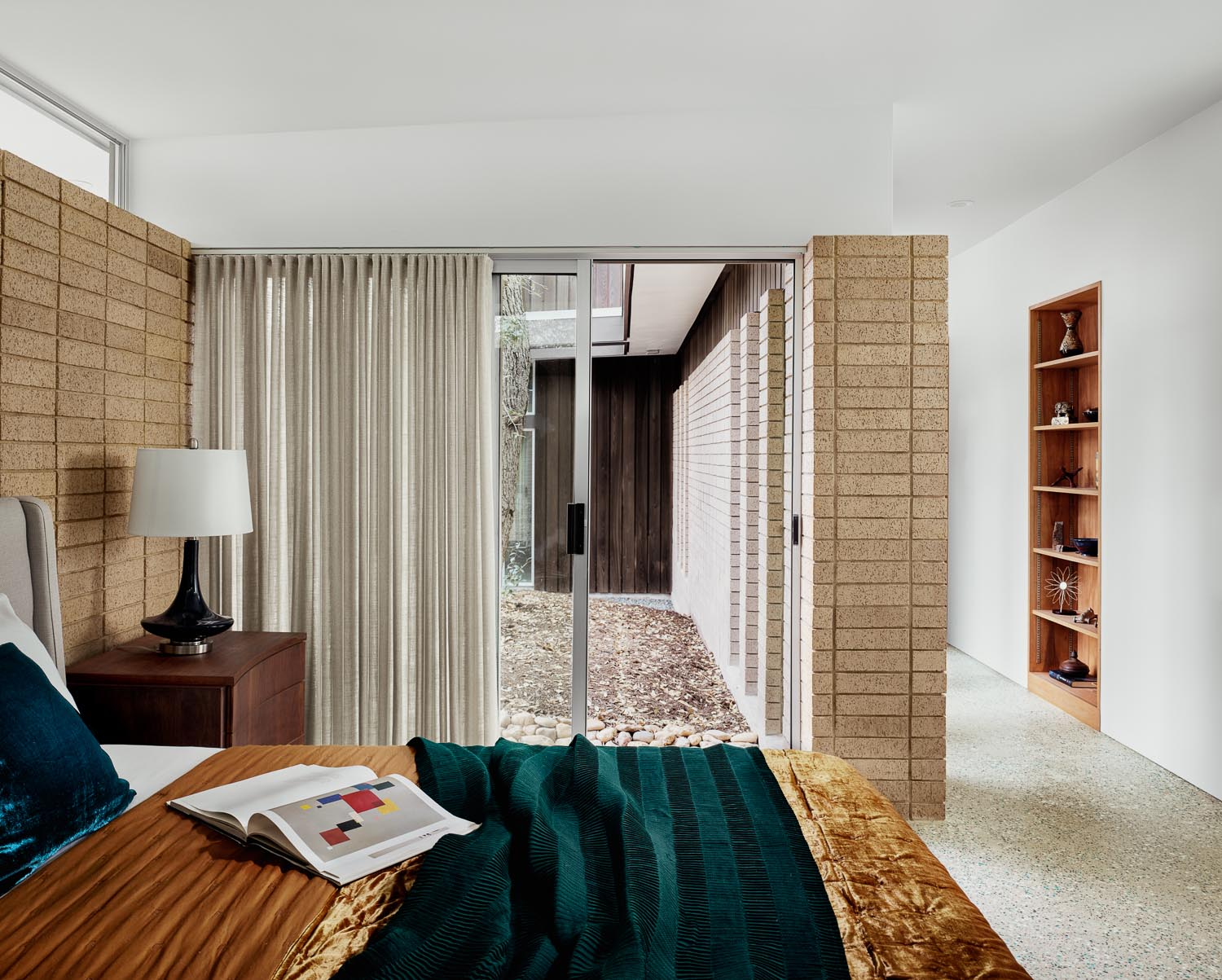 A sliding glass door in this mid-century modern inspired bedroom connects the space with the outdoors.