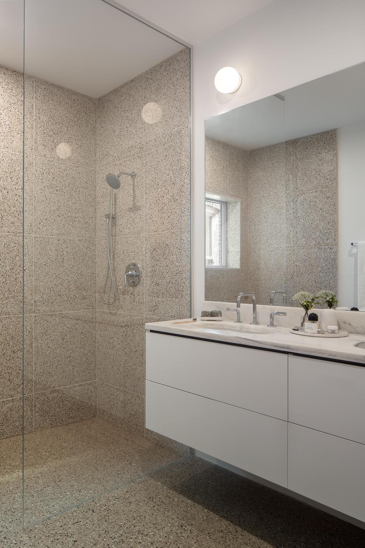 This modern bathroom features large format tiles and a white vanity.
