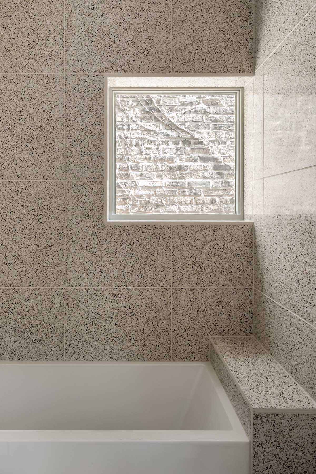 This modern bathroom features large format tiles and a built-in bathtub.