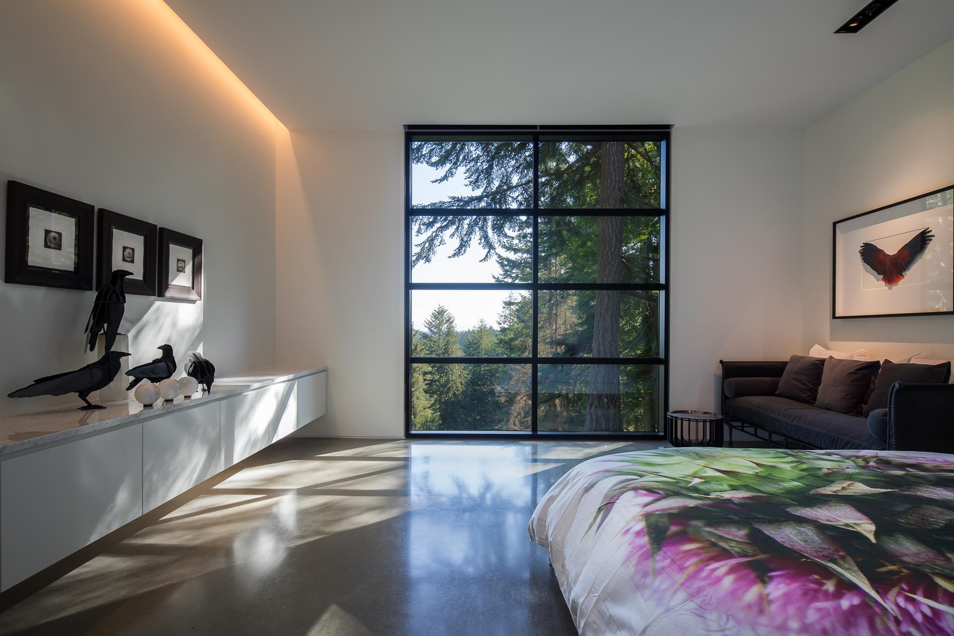 This modern bedroom has a section of floor-to-ceiling black framed windows, while hidden lighting is used to create indirect light.