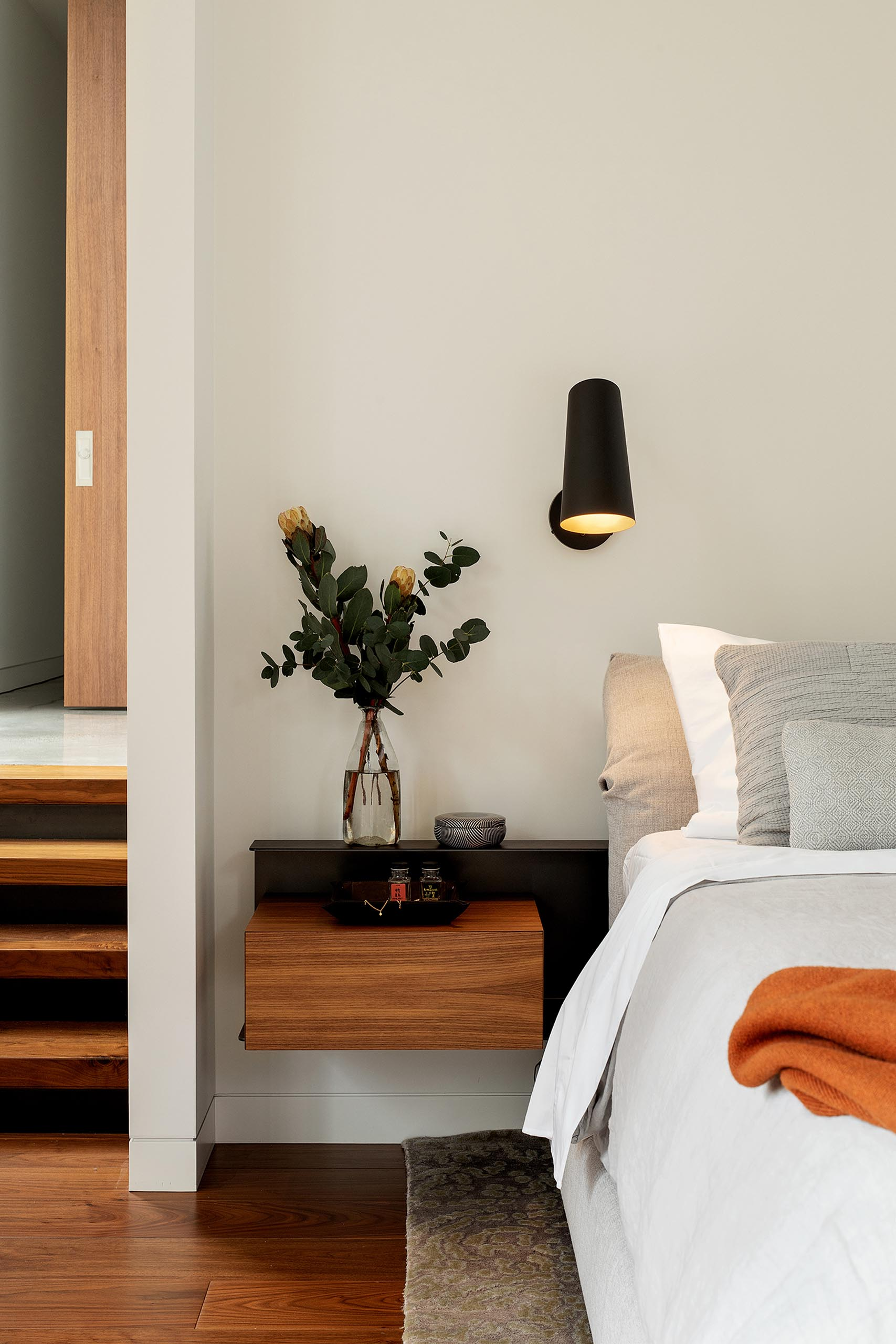A modern bedroom with a floating bedside table and matte black sconce.