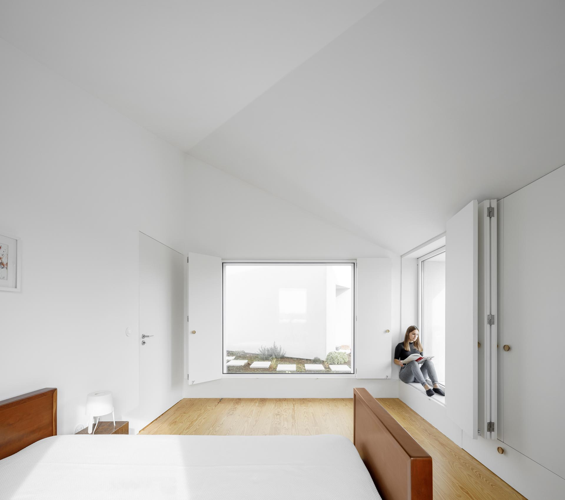 A modern bedroom with minimalist furnishings and folding window shutters.