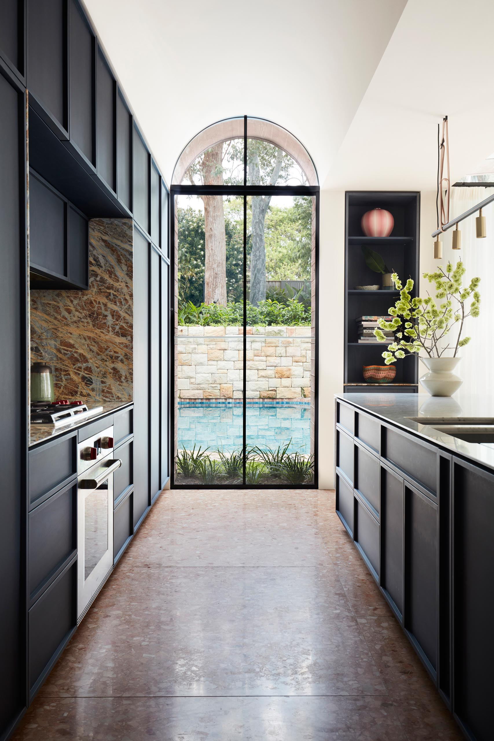 A modern kitchen with dark hardware free cabinets, and a large arched window with views of the swimming pool.