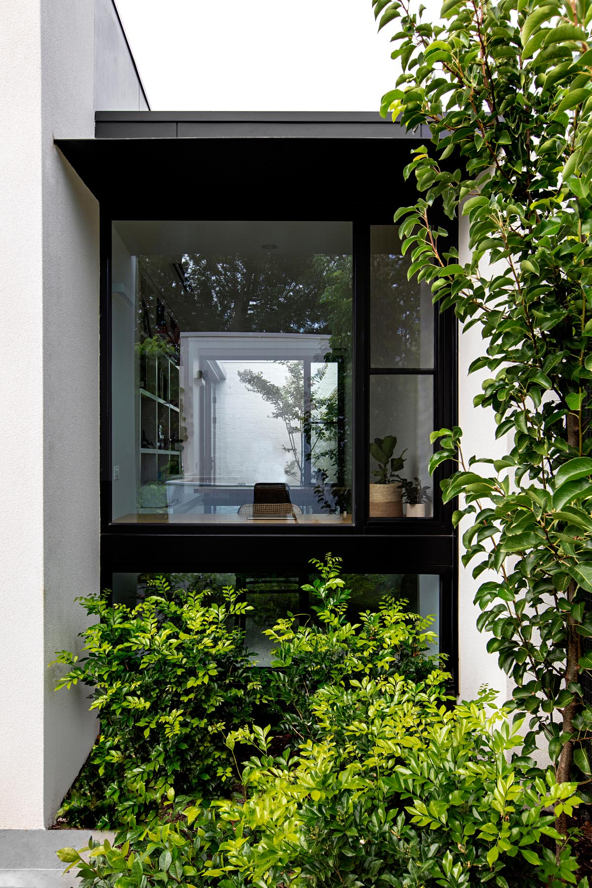 A home office with black window frames that has views of the garden.