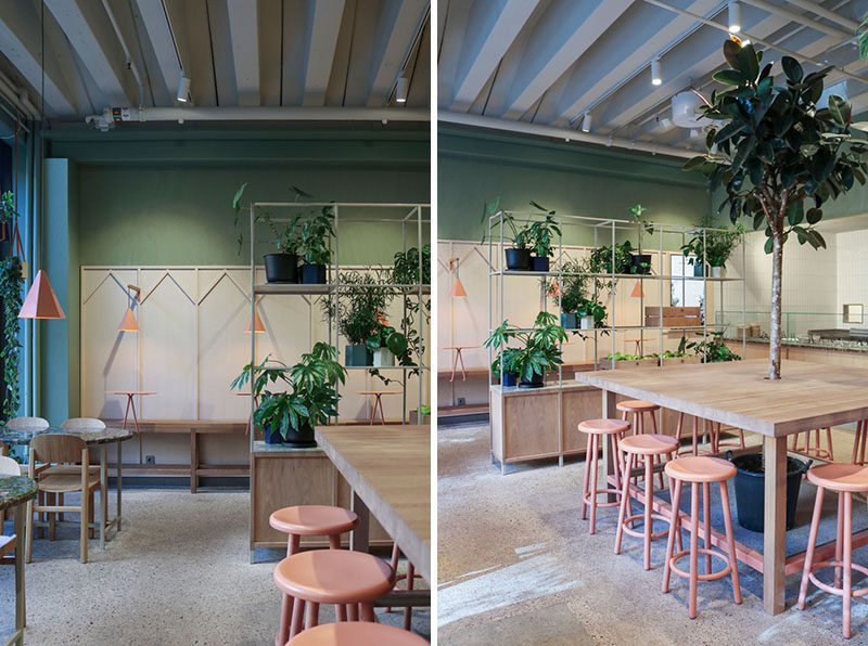 The community-style oak table features a tree at the centre of this restaurant, while open grid shelves are used to subdivide the space using green plants. #RestaurantInterior #InteriorDesign