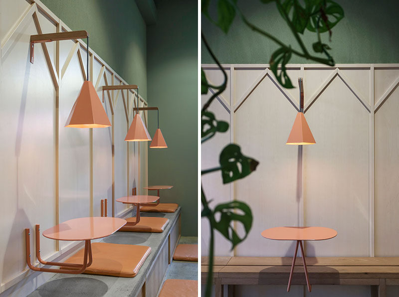 The walls are lined with long oak and concrete benches, and wall-mounted salmon pink tables and lights. #RestaurantInterior #RestaurantDesign