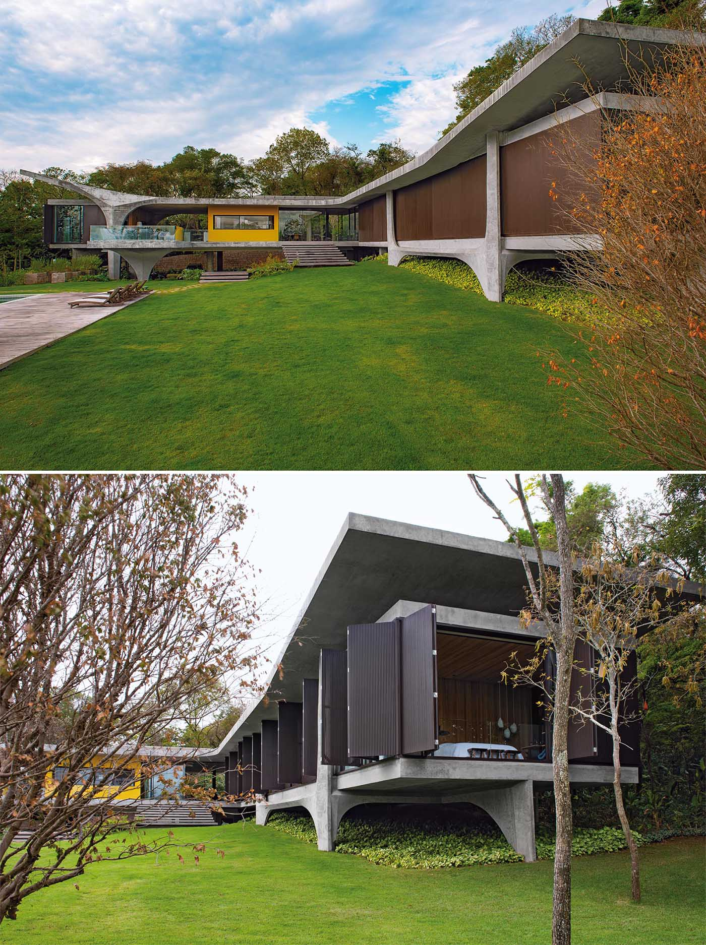 The design of this modern concrete house allows the form to somewhat appear as though it floats over the terrain, while the pillars add a sculptural element.