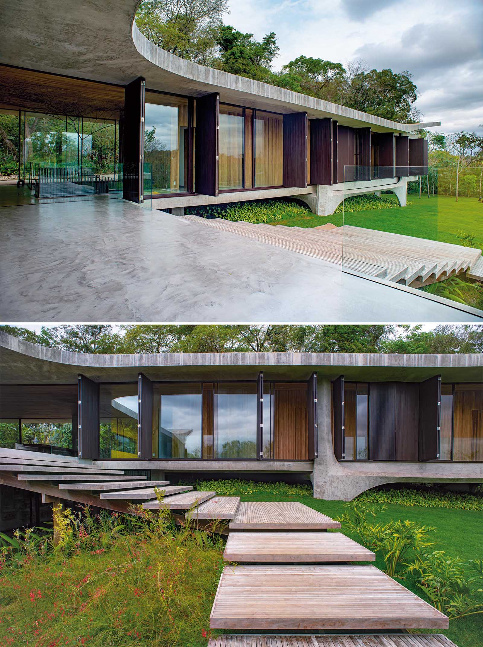 This modern concrete house has wood stairs that lead from the main living level down to the yard and swimming pool.