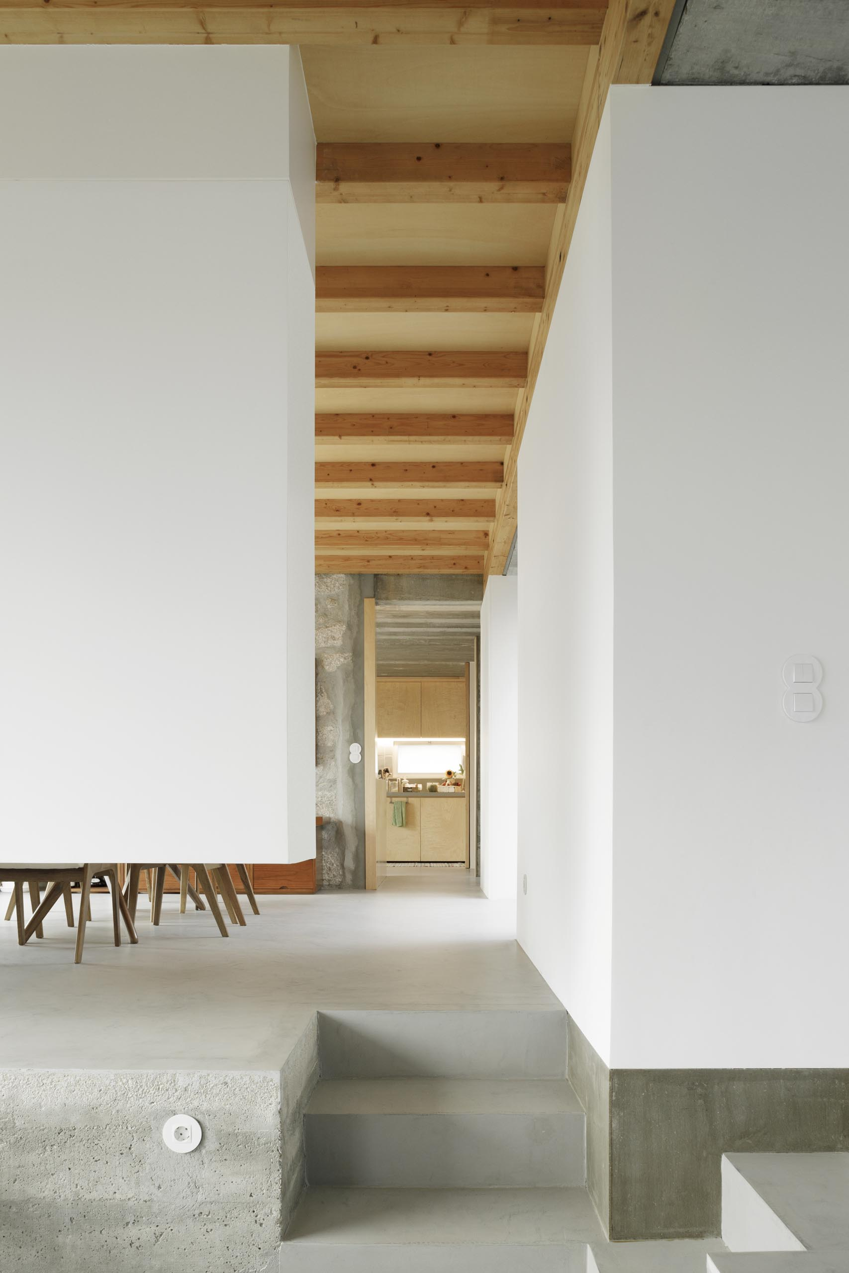 A modern home with concrete floors, white walls, and a wood ceiling.