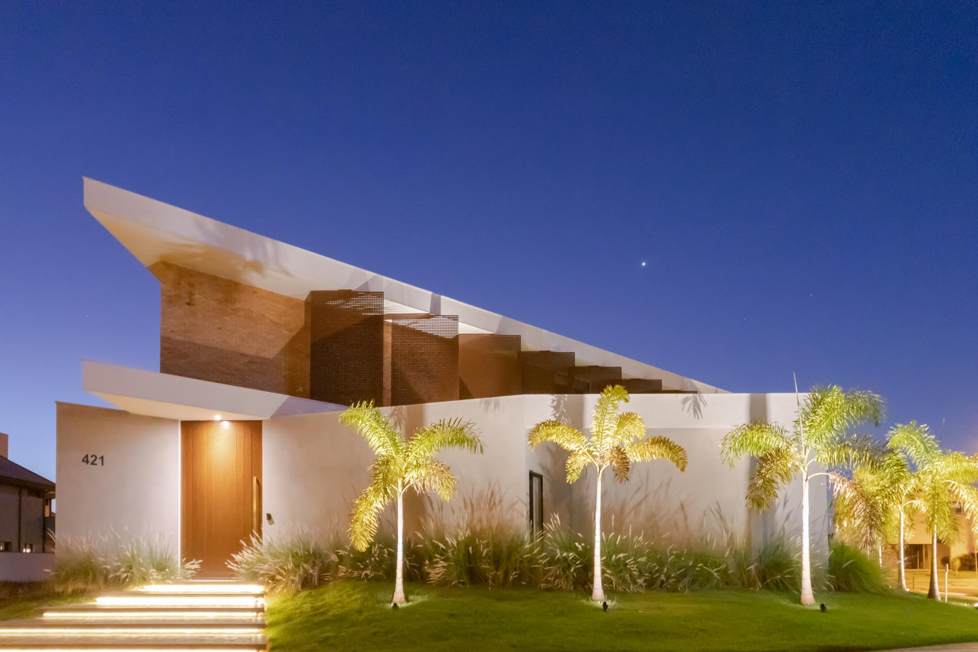 This modern home is located on an irregular corner lot, with the curb appeal showcasing steps with hidden lighting, and uplighting the palm trees.