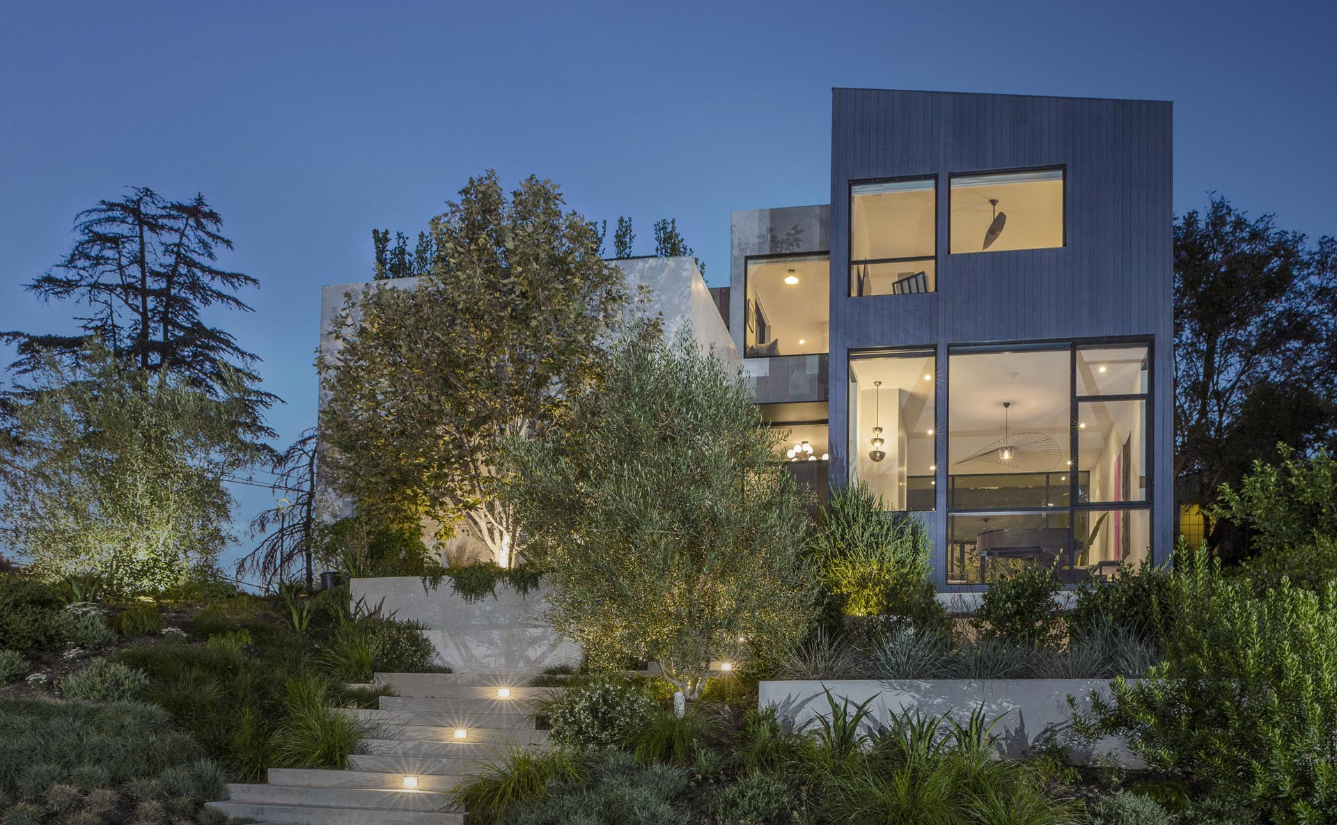 Mature landscaping is separated by concrete stairs that lead up to the house, and at night, lighting creates a guided path.