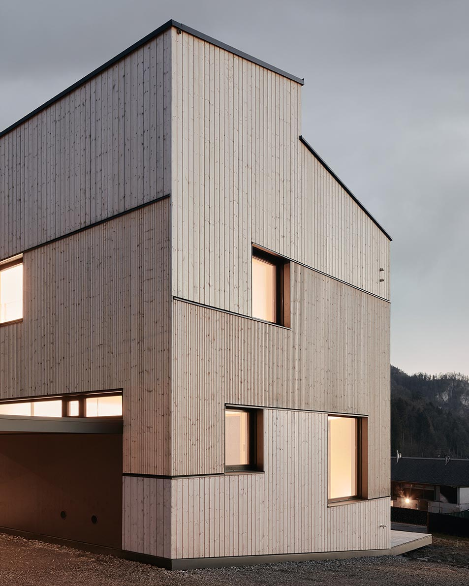 A modern wood duplex with different sizes of natural wood siding and black accents.