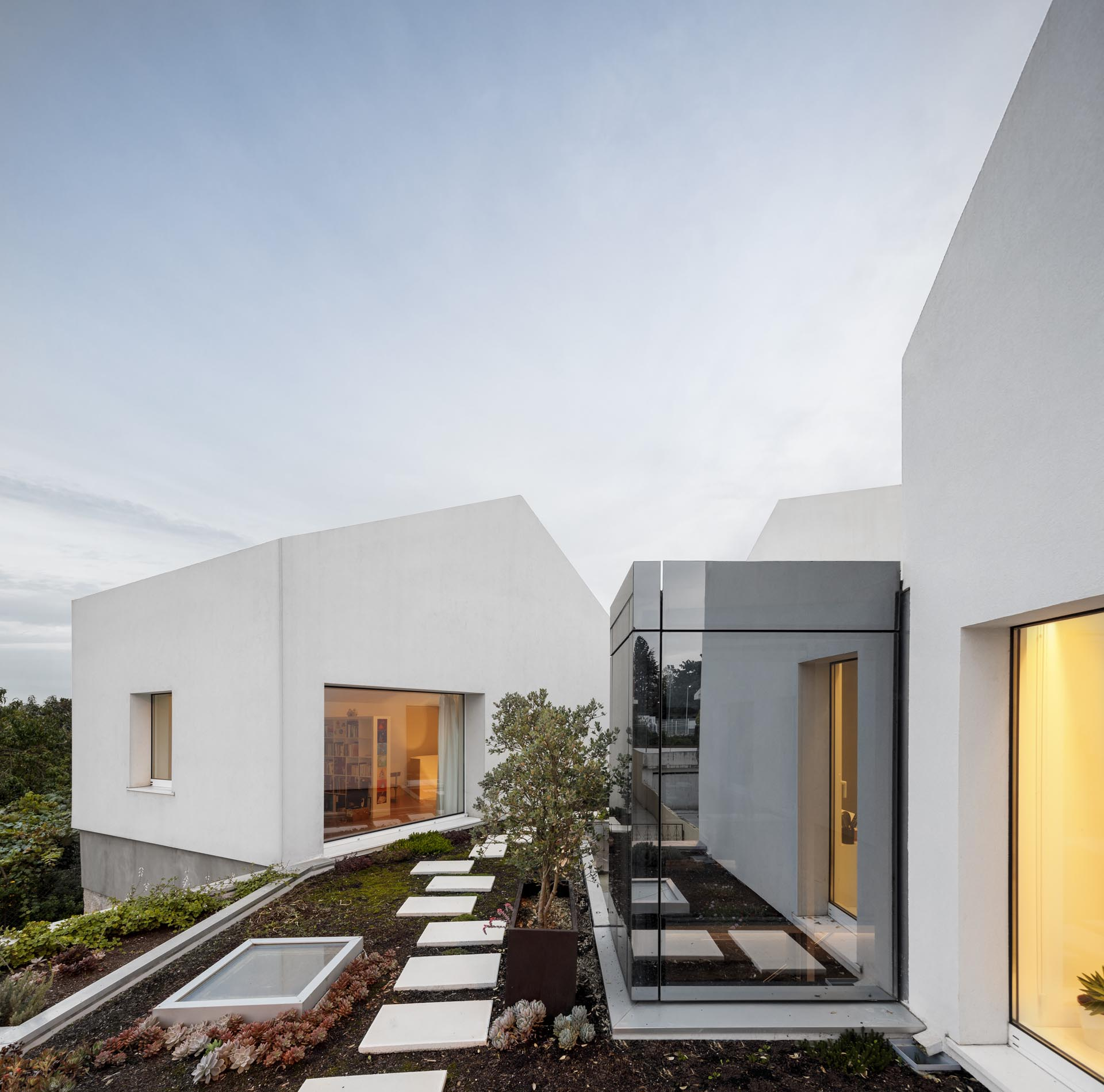A modern home with stone walls, concrete and wood accents, and a rooftop garden.