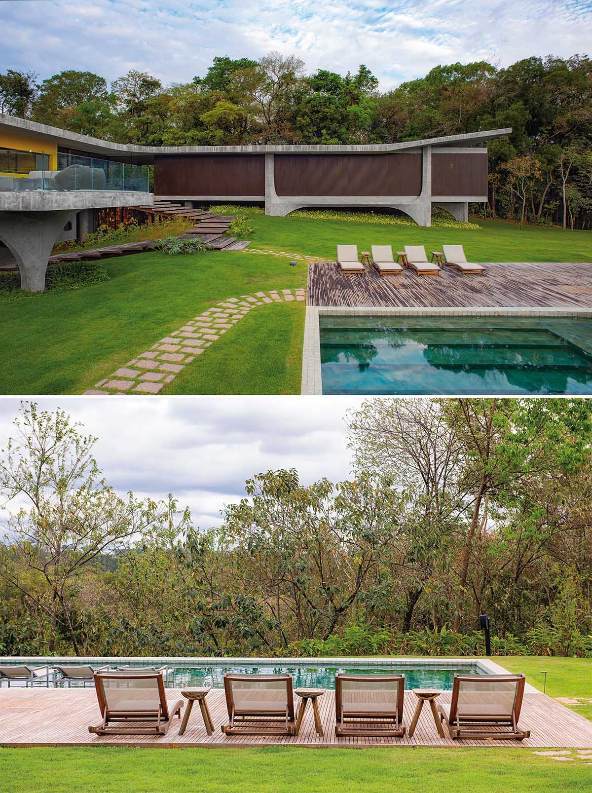This modern concrete house has wood stairs that lead down to a swimming pool and deck.