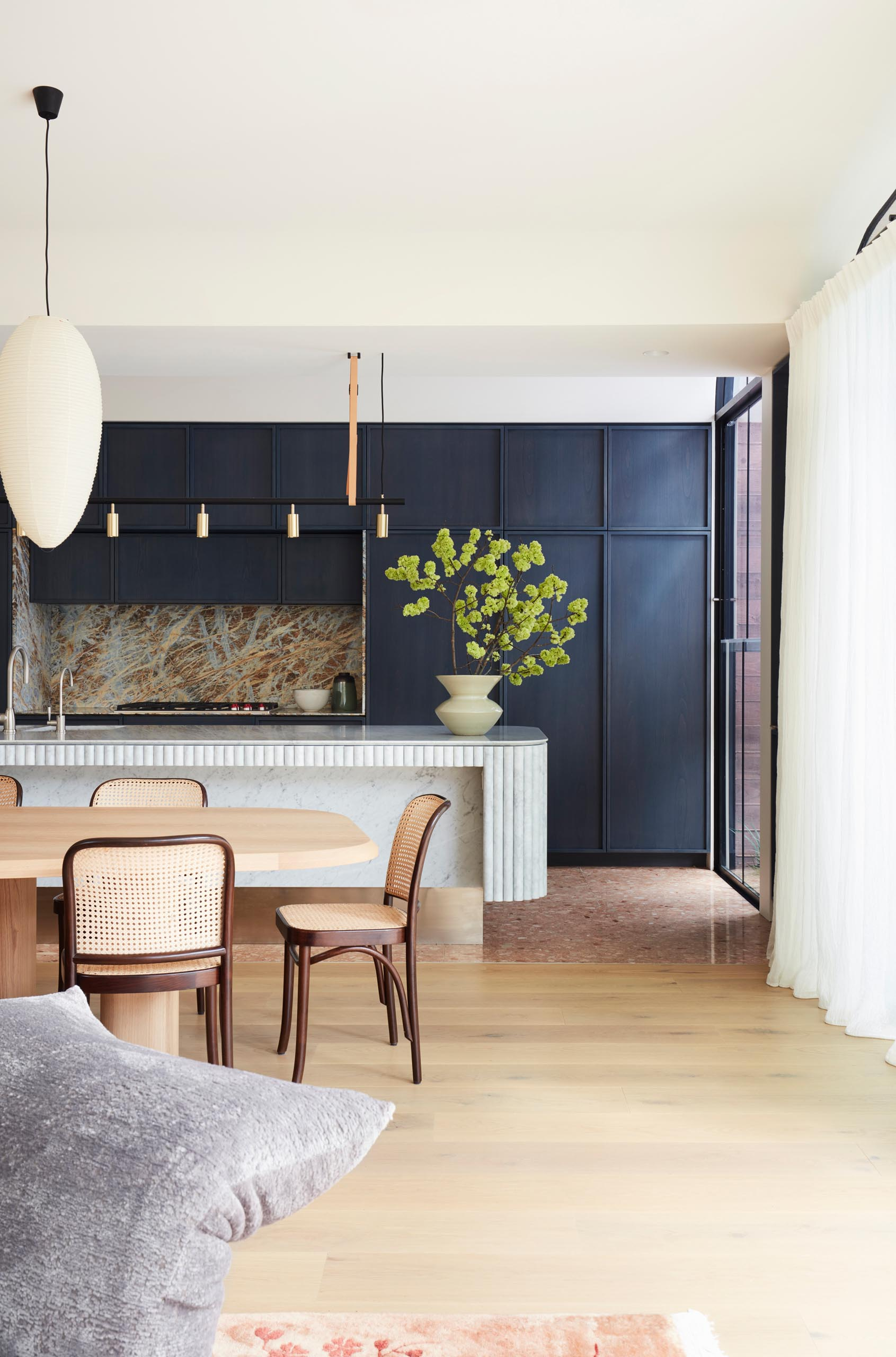 A modern kitchen with dark hardware free cabinets, and a curved island.