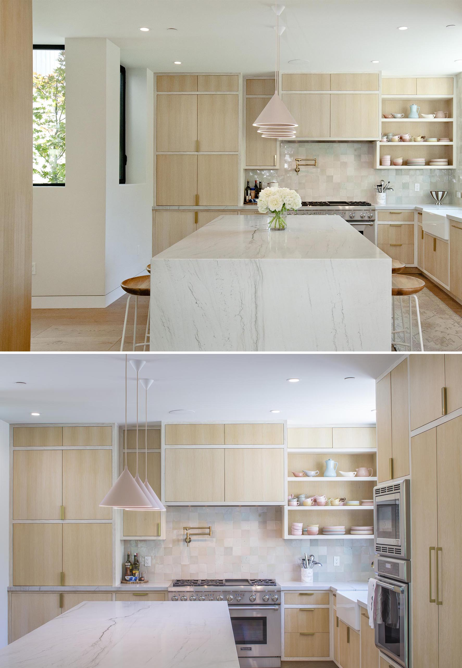 In this modern kitchen, light wood cabinets sit flush within their frames, while an island has a waterfall countertop, and the pastel pink pendant lights complement the displayed dishware and the backsplash.