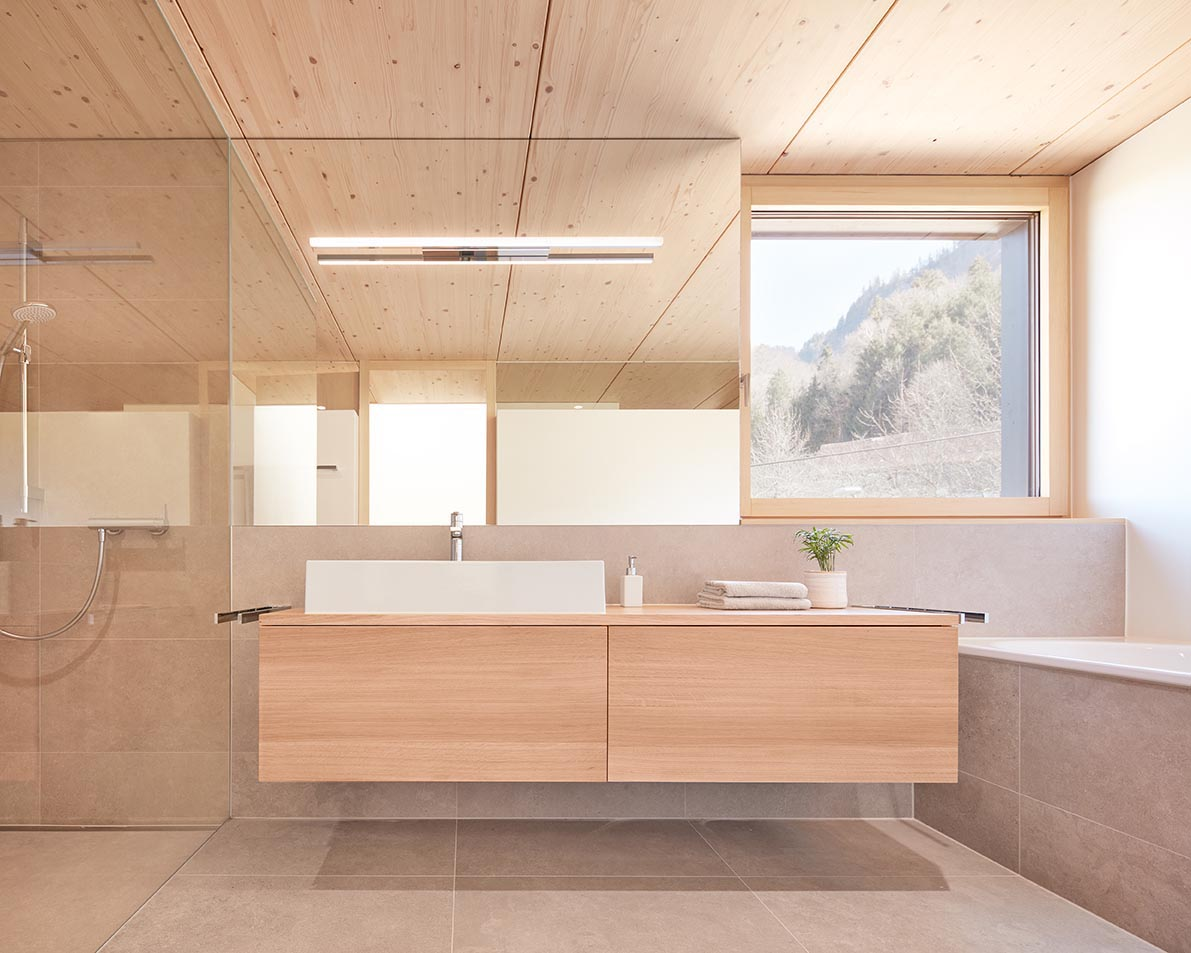 In this modern bathroom, a square window creates a picture perfect view of the trees, and the floating wood vanity separates the shower and the built-in bath.