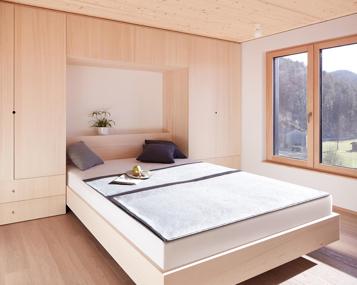 In this bedroom, built-in closets and drawers flank either side of the bed.