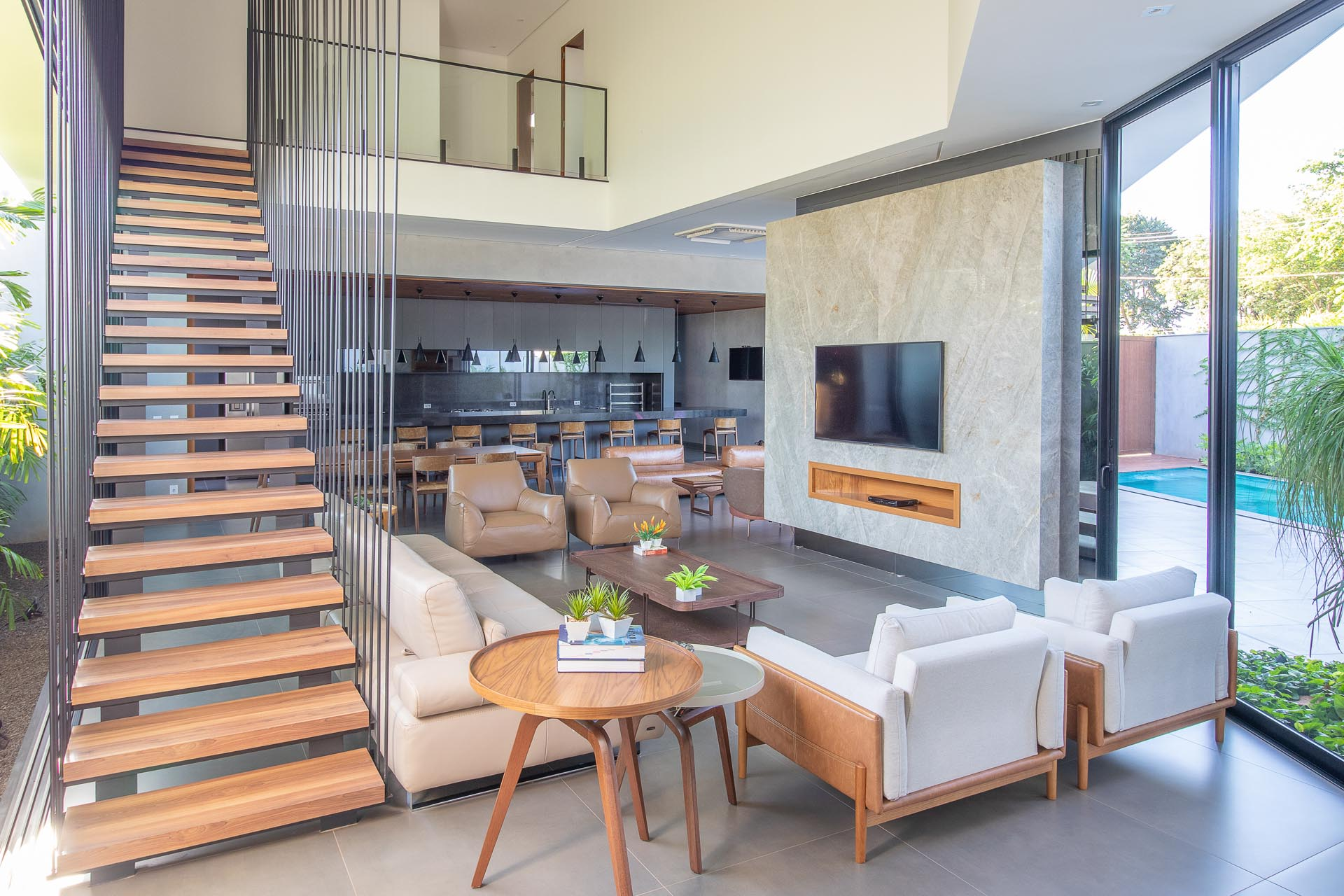 This mdoern living room is flooded with natural light from the oversized windows and sliding doors, while the stairs draw attention to the double height ceiling.