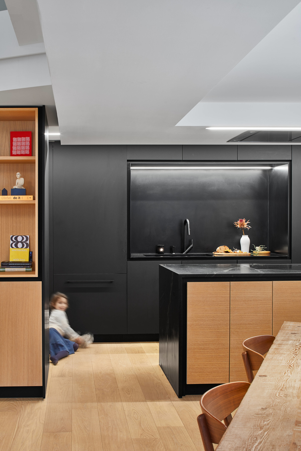 A modern matte black kitchen with hardware free cabinets and a large island with wood accents.