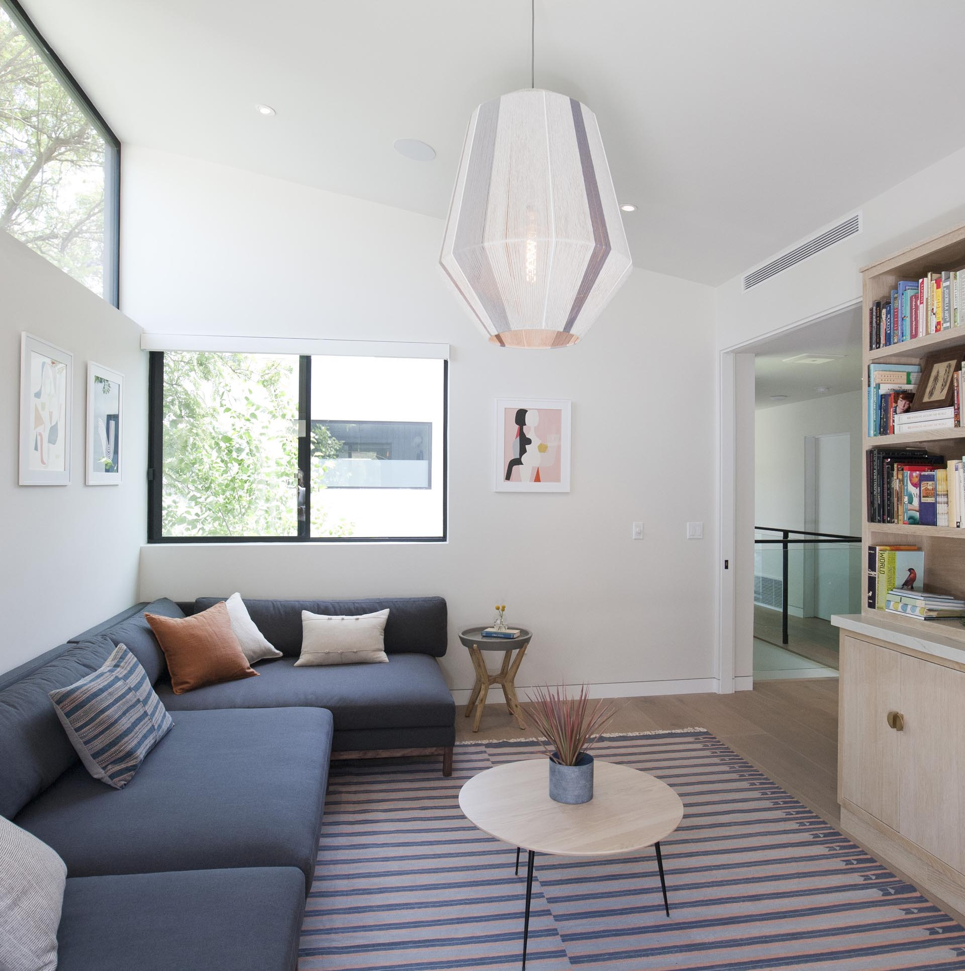 In his modern casual living / reading room, there's a dark gray sofa and a cabinet with open shelving filled with books.