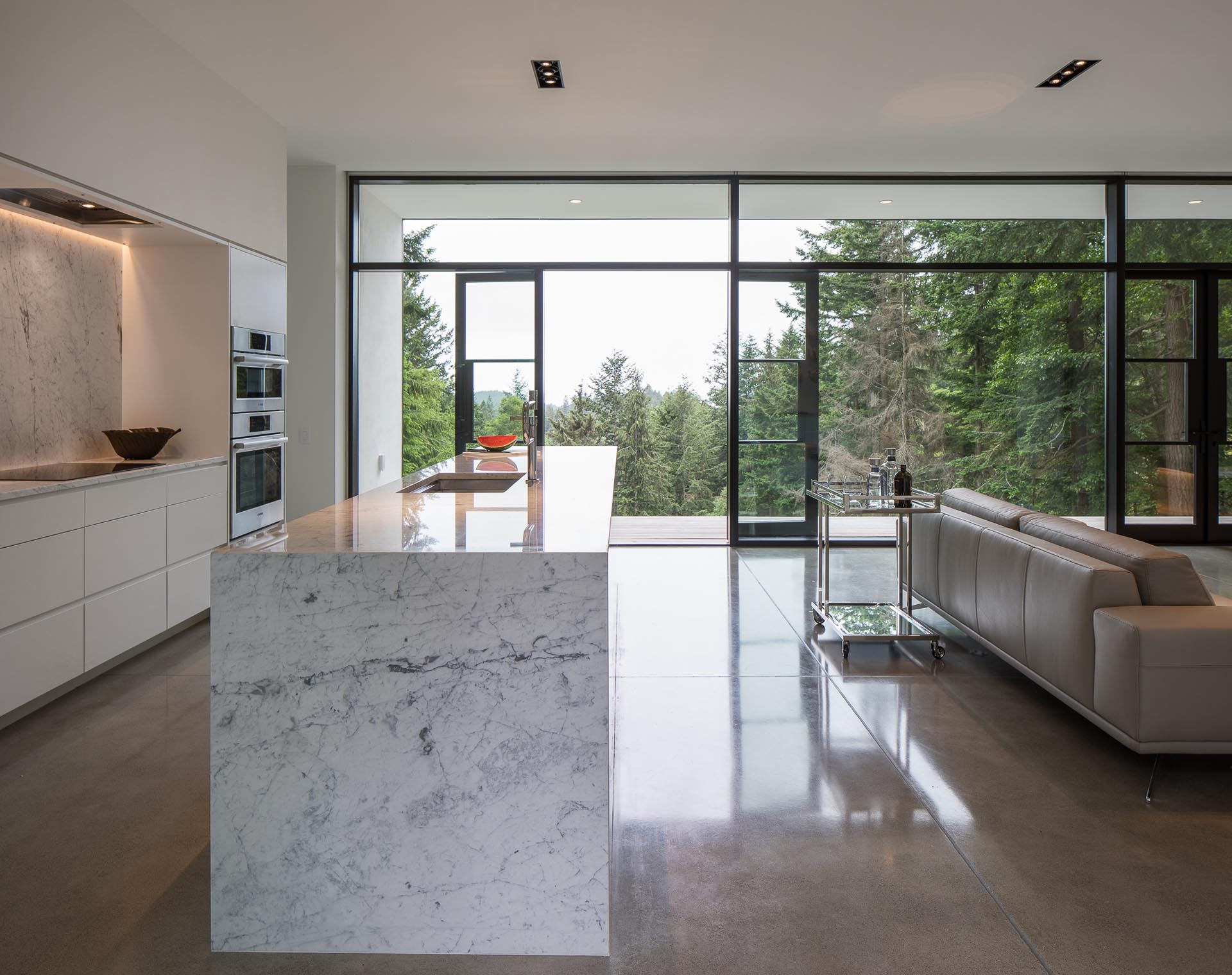 A modern kitchen with minimalist white cabinets, Carrera marble countertops, and gray concrete flooring.