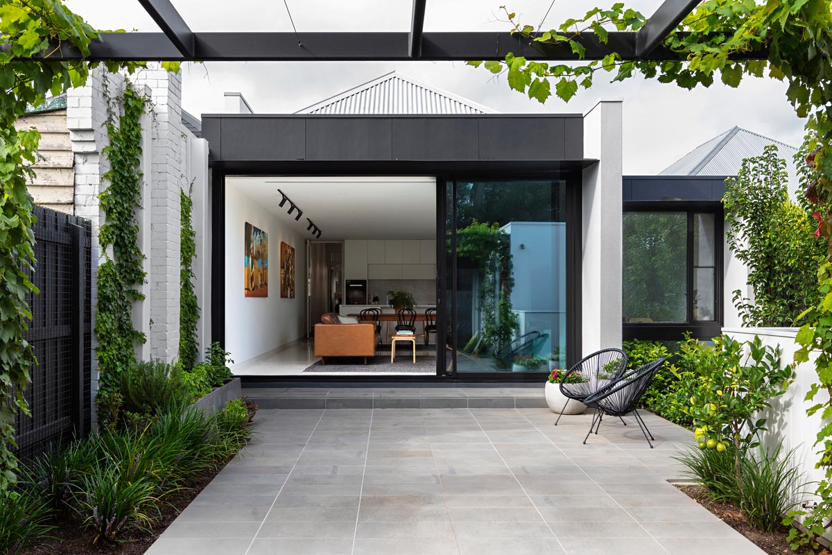 A modern rear addition that has a partially covered patio and large sliding glass doors.