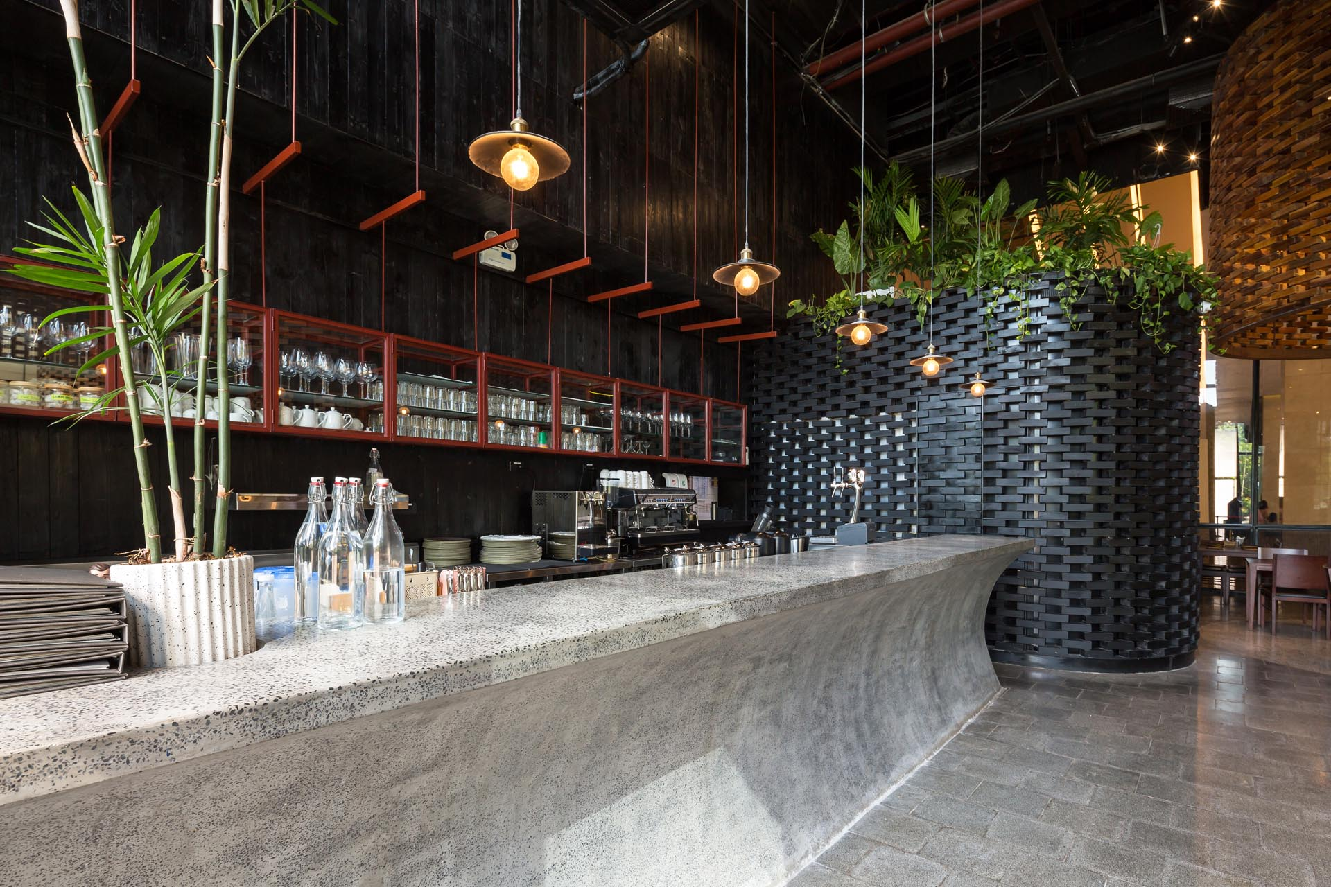 A modern restaurant with a curved concrete bar.