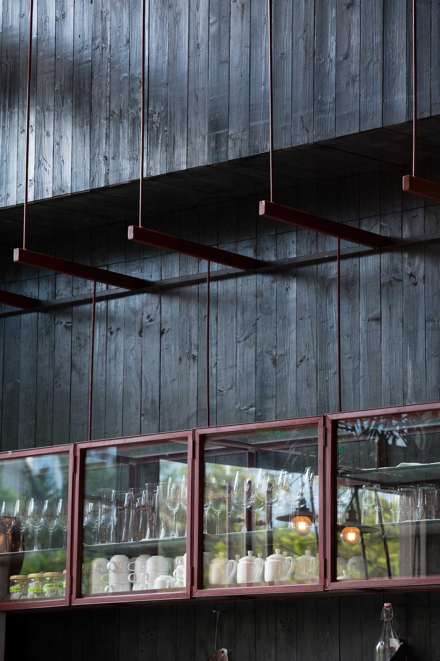 A modern restaurant with black wood walls and a glass display cabinet.