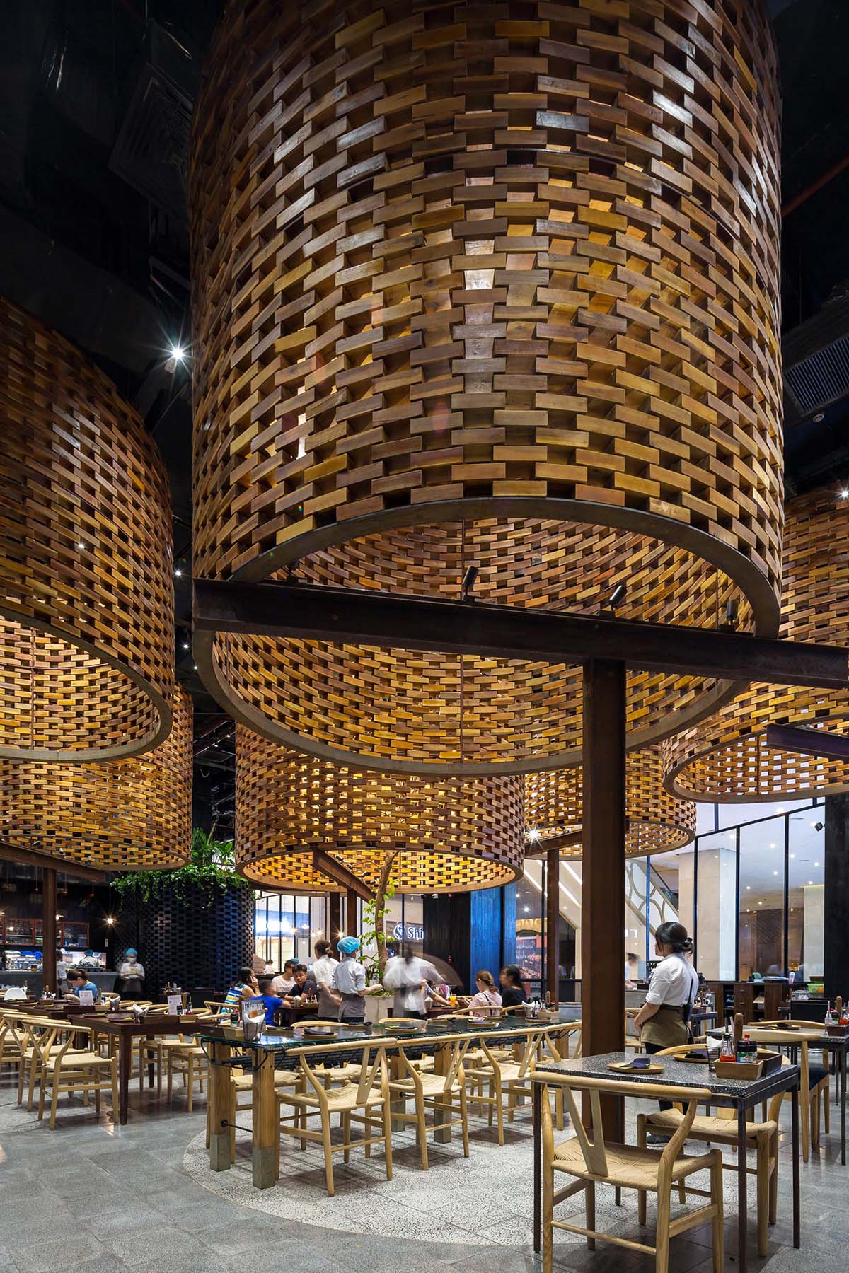 A modern restaurant with large sculptural cylinders made from wood bricks.