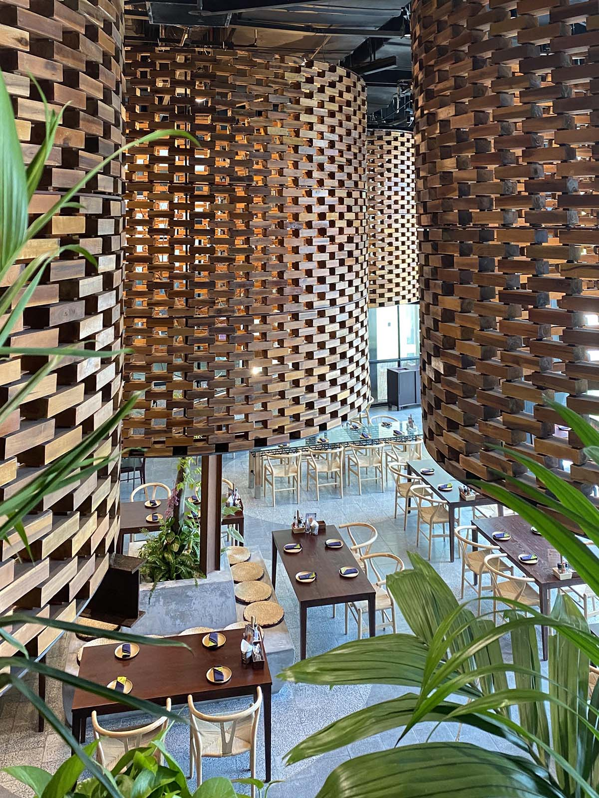 A modern restaurant interior design with large sculptural cylinders made from wood bricks, and contemporary wood furniture.