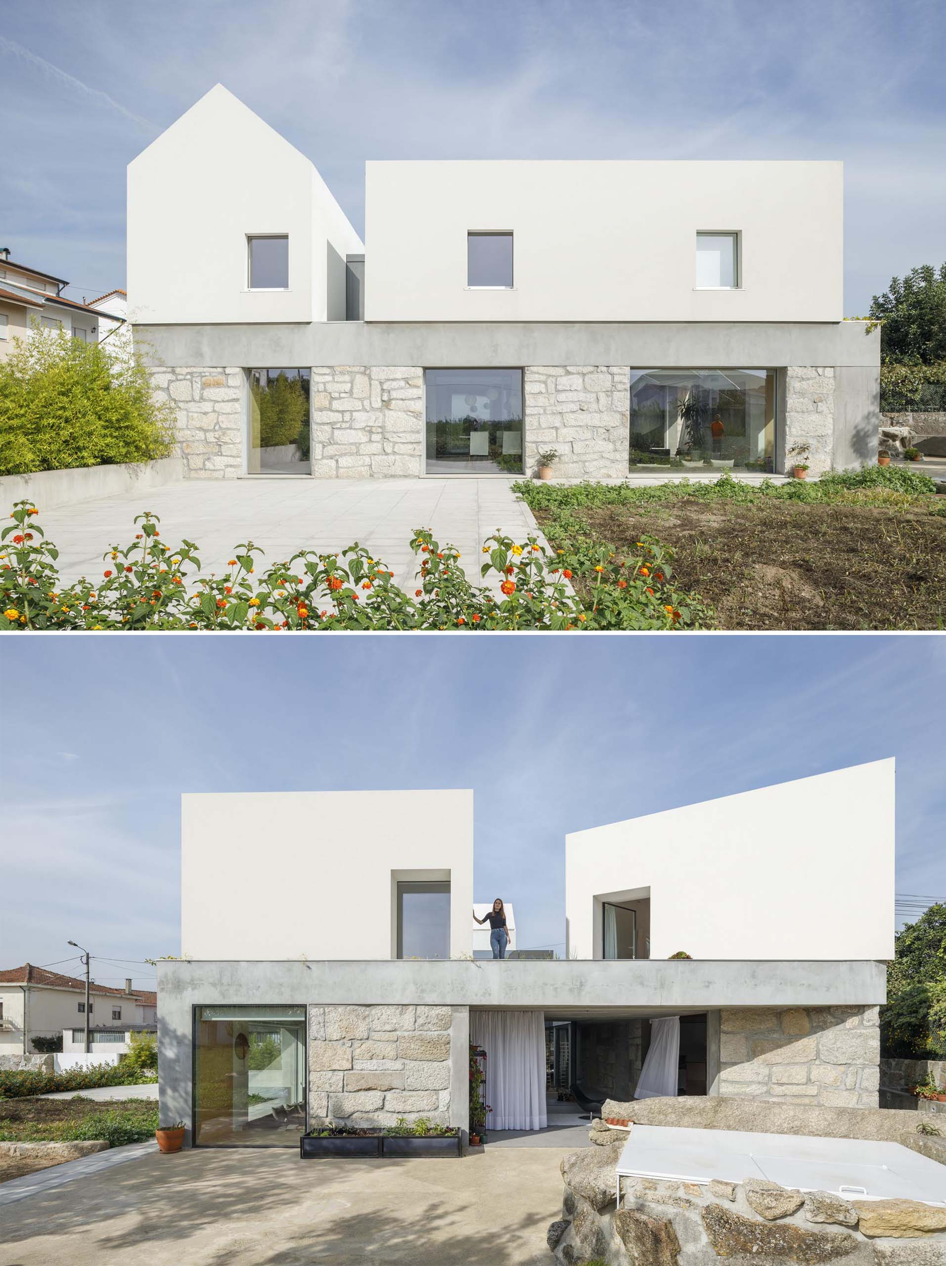 A modern home with stone walls, and a white upper floor.