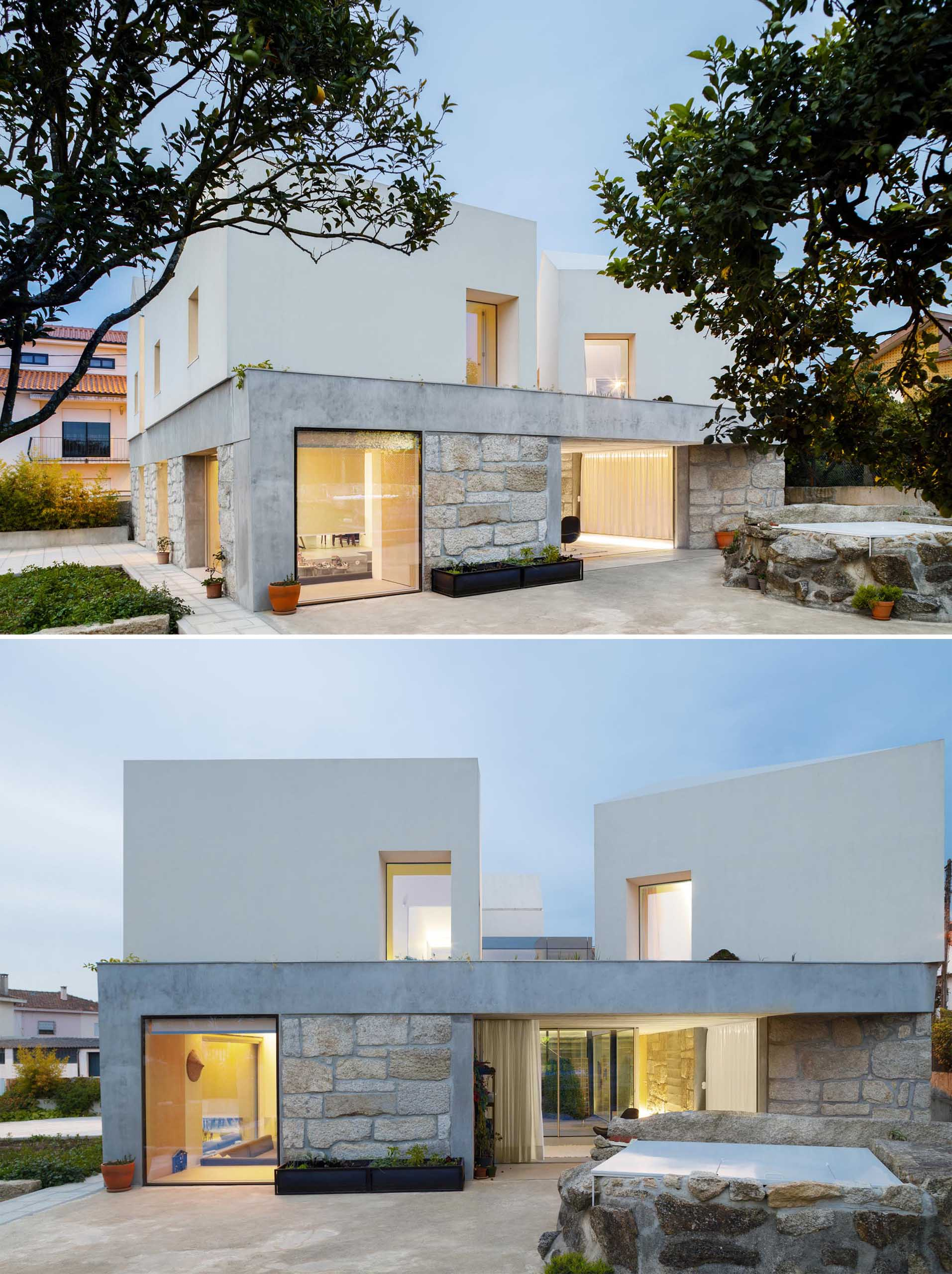 A concrete slab separates the stone walls and white upper portion of this modern home.