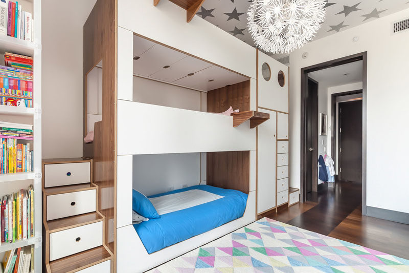 This modern triple bunk bed has two dedicated sets of stairs for the middle and top bunks, built-in storage, and hanging tray tables for each bed. #BunkBed #TripleBunkBed #KidsRoom #Bedroom #ModernBedroom