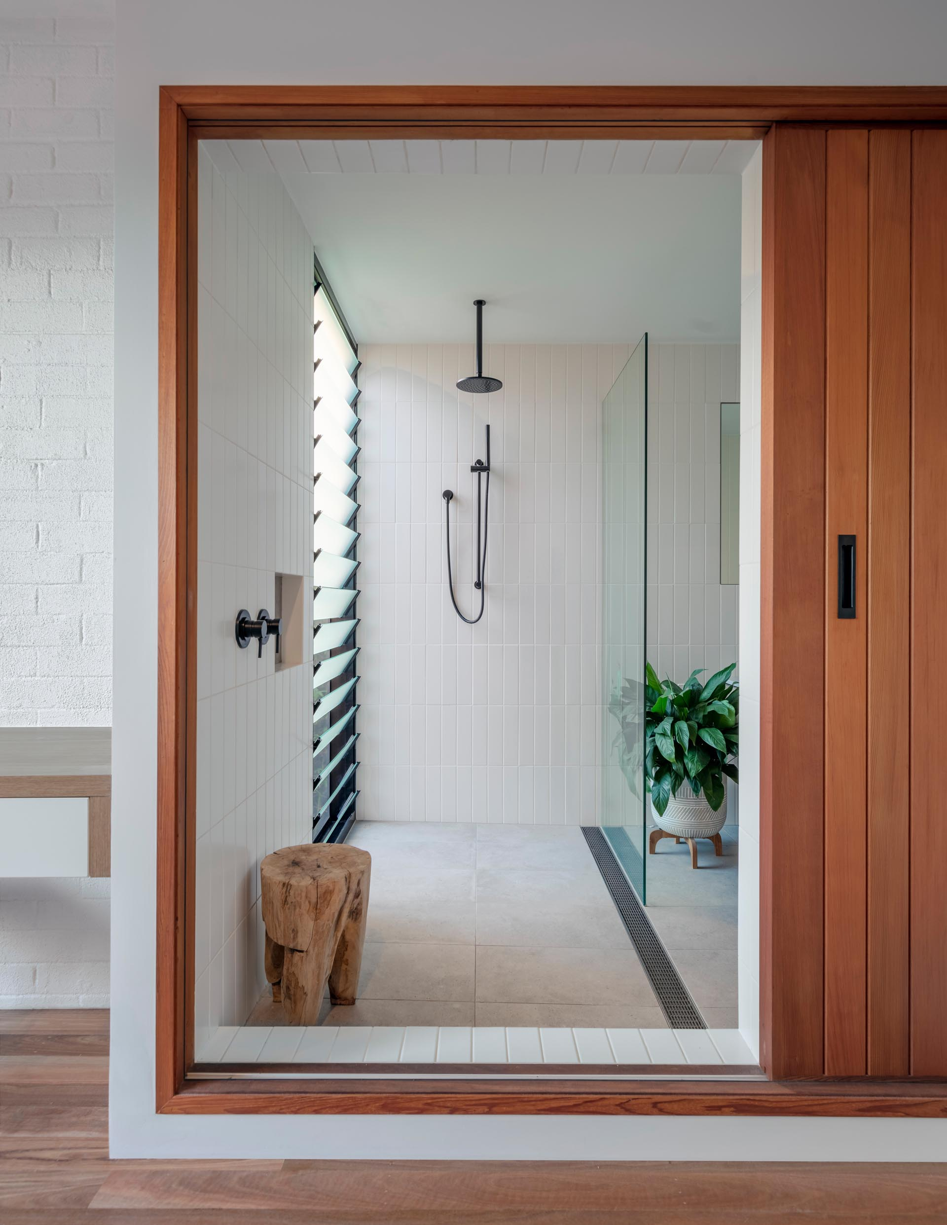A modern bathroom with white rectangular tiles and a louver window in the shower.