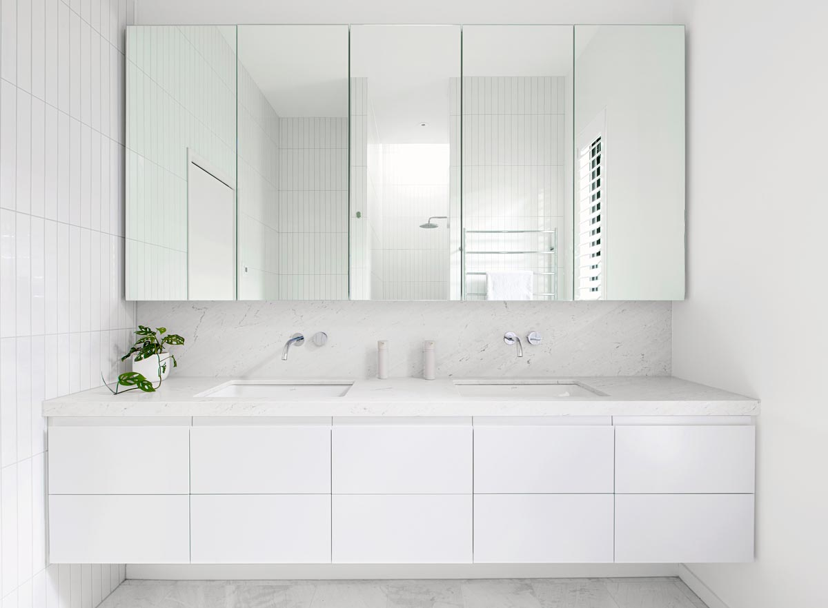 In this modern all white bathroom, honed Carrara Bianco marble was used for both the vanity countertop and the flooring.