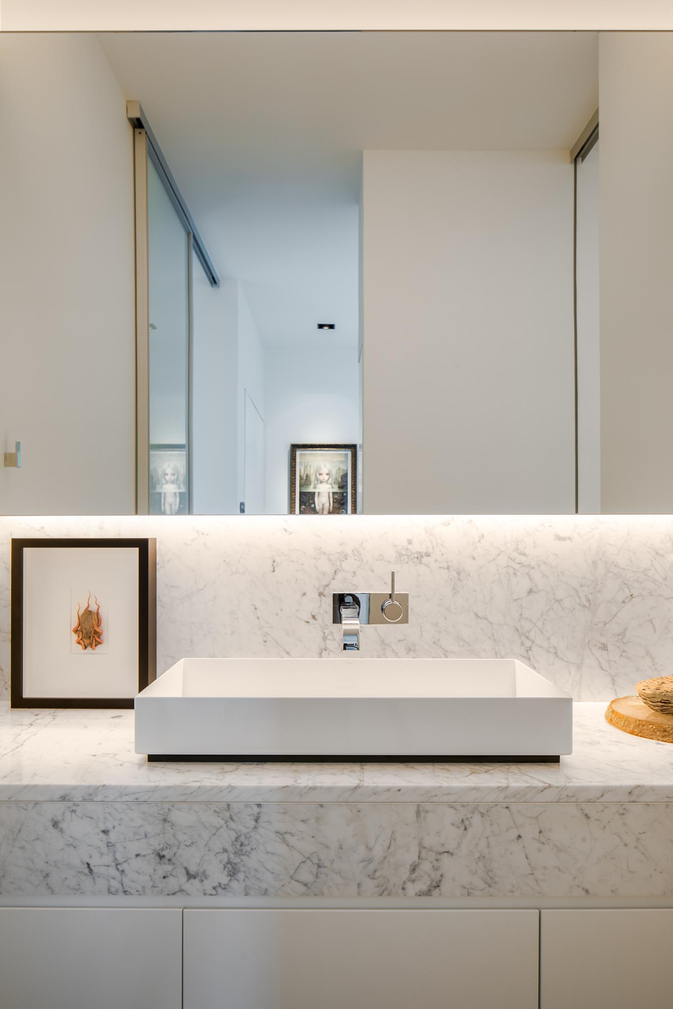 This modern en-suite bathroom has a backlit mirror, a floating vanity, and a walk-in shower with a shelving niche.