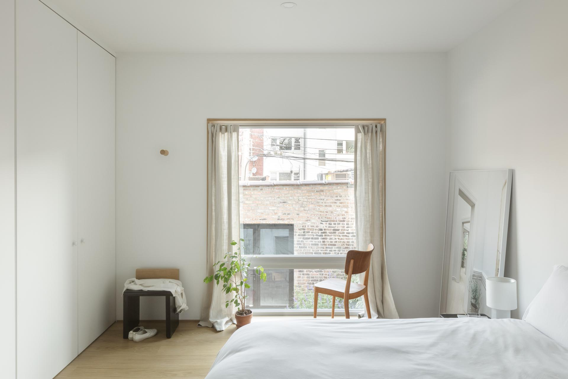 In this bedroom, minimal furnishings match the white interior, while the wood window frame complements the wood flooring.