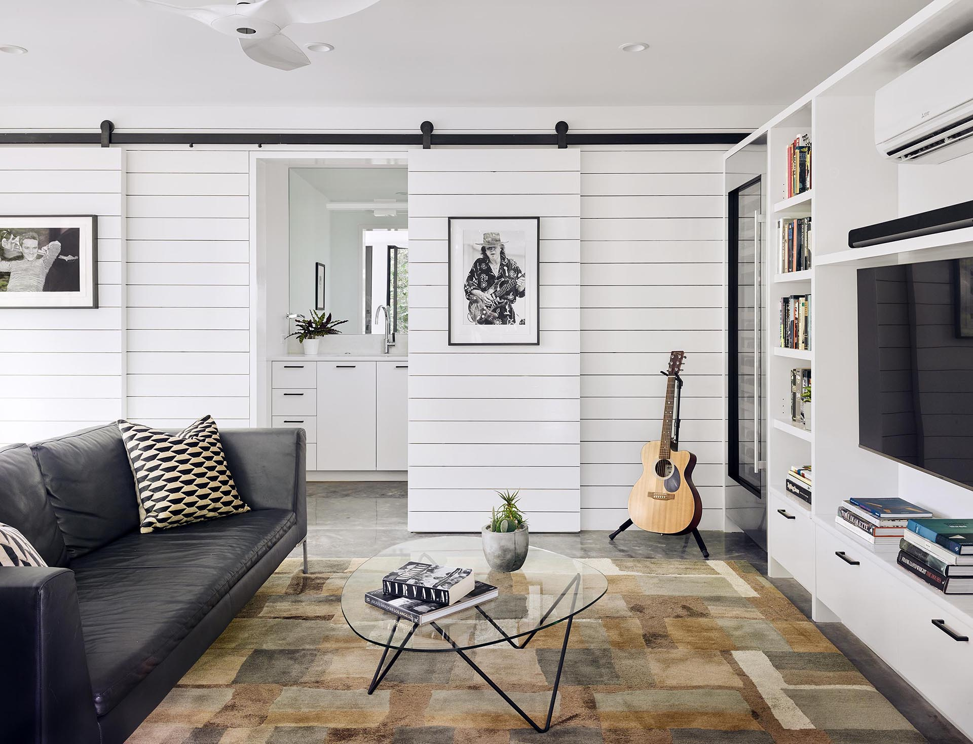 A modern living room with white walls, sliding barn doors, and a custom shelving unit that surrounds a television.
