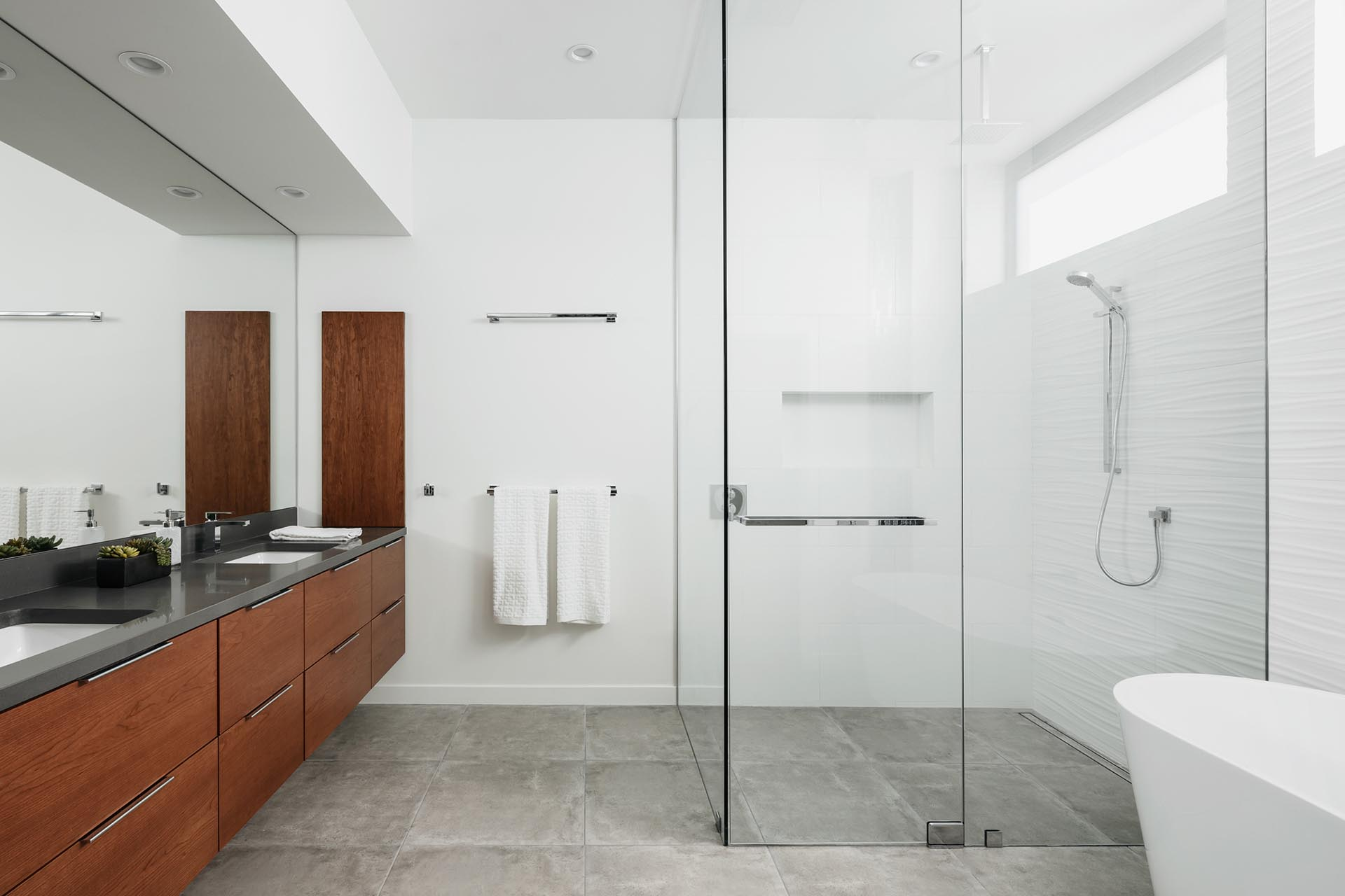 In this modern master bathroom, a floating wood vanity is topped with dark gray quartz counters, a step free shower with frameless glass is positioned in the corner, and an adjacent free-standing tub has a backdrop of a 3d tile wall.