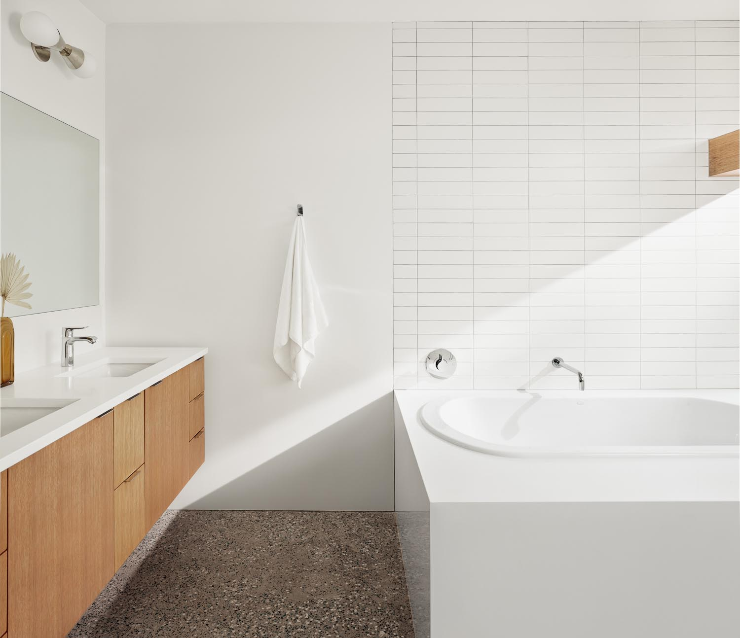 In this modern bathroom, there's a floating wood vanity, a built-in bathtub, and walls lined with white rectangular tiles.
