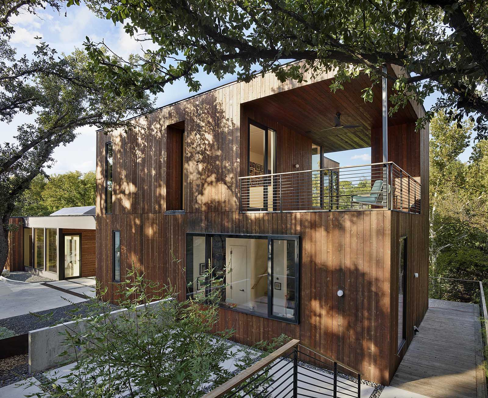 A modern home addition with a green roof and a wrap-around deck.