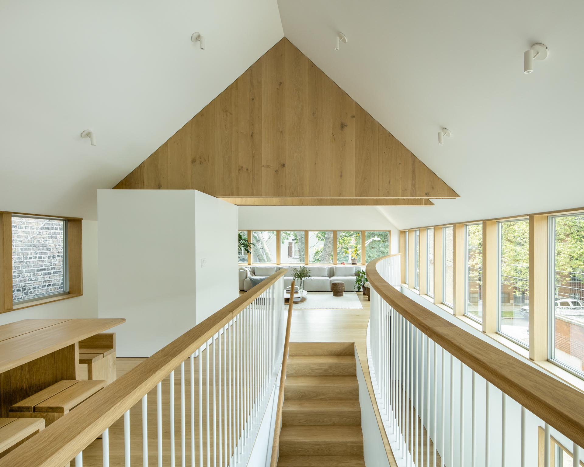 Wood stairs with a matching handrail and railing lead up to the social areas of this modern home.